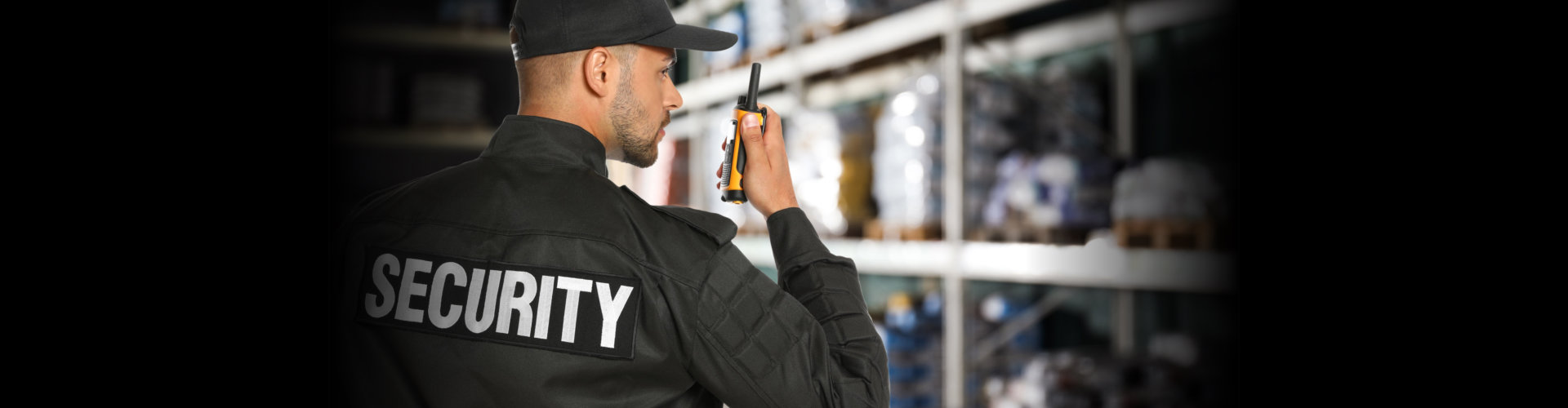 Security guard using portable radio transmitter in wholesale warehouse